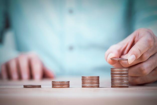 Mão do empresário colocando moedas em pilhas de moedas na mesa de madeira e fundo de camisa de hortelã