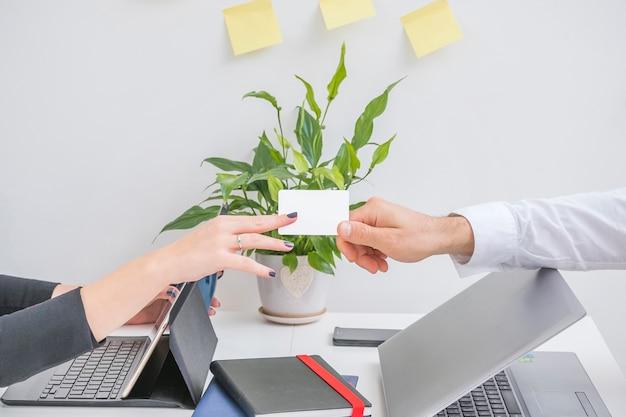 Mão do empresário dando cartão para seu parceiro no escritório