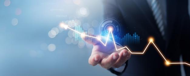 Mão do empresário de terno segura gráfico de finanças de negócios bancários em desfoque suave de fundo azul