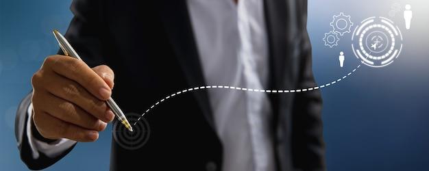 Mão do empresário de terno segurando uma caneta e desenhando um gráfico crescente para o sucesso