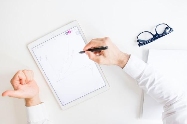 Mão do empresário desenho gráfico com caneta na tela gráfica digital tablet mostrando o polegar para cima o sinal