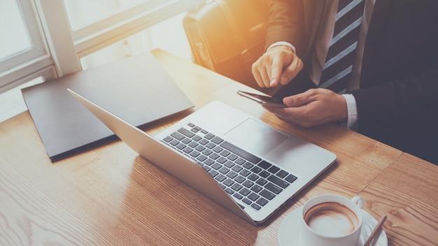 Mão do empresário digitando no smartphone com laptop e xícara de café