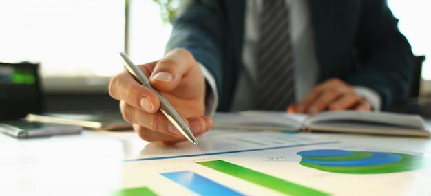 Mão do empresário em terno de enchimento e assinatura com