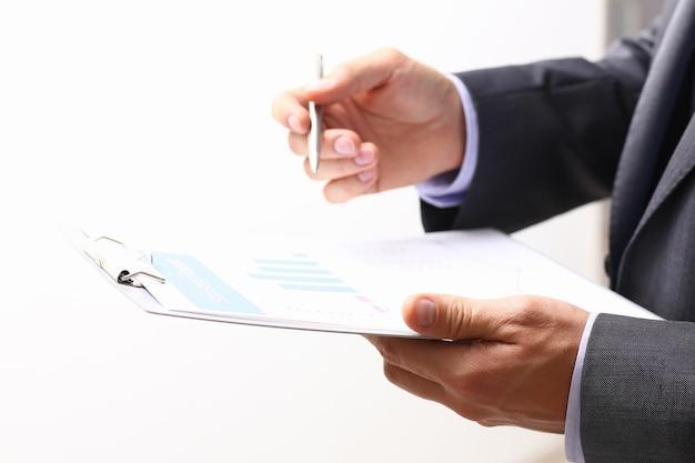 Mão do empresário em terno preenchendo e assinando contrato de parceria com caneta de prata