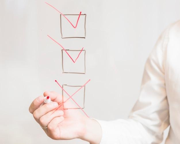 Mão do empresário marcando cruz na caixa de seleção com marcador sobre a tela
