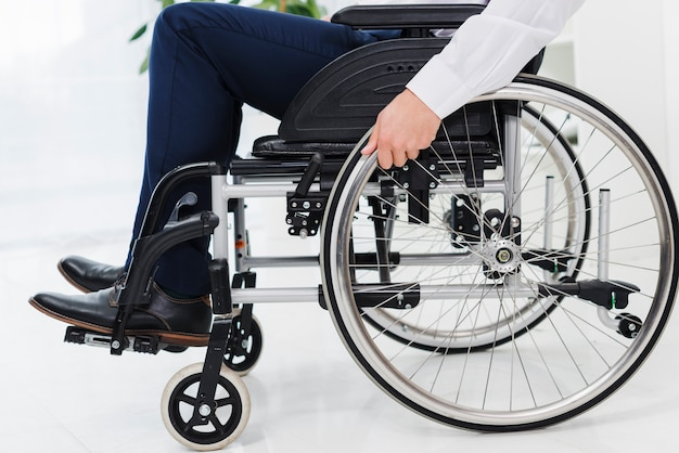 Mão do empresário na roda sentado na cadeira de rodas