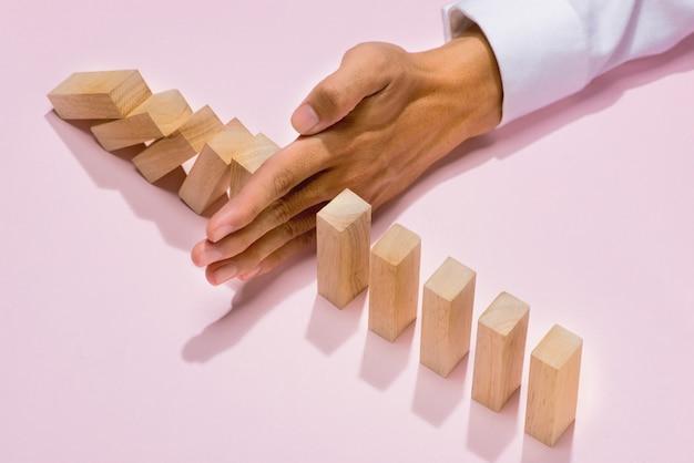 Mão do empresário parar dominó continuamente derrubado