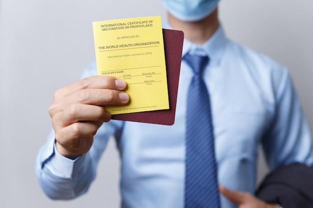 Mão do empresário segura passaporte de certificado de vacinação para viagens ou negócios, covid-19 e conceito de saúde.