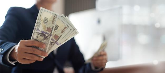 Mão do empresário segurando a nota de banco no escritório.