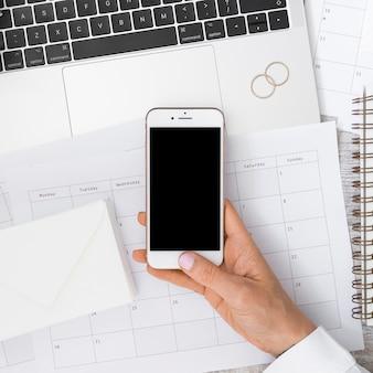Mão do empresário segurando smartphone sobre o calendário com envelope; laptop e alianças de casamento
