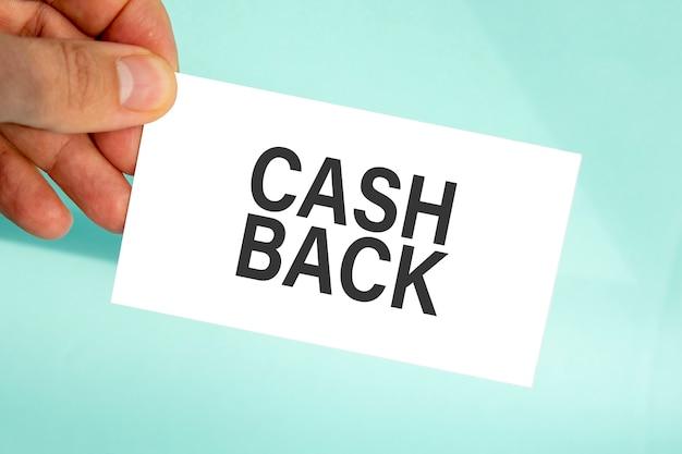 Mão do empresário segurando um cartão de visita de papel com o texto devolução de dinheiro, plano de fundo azul claro de close up, conceito de negócio