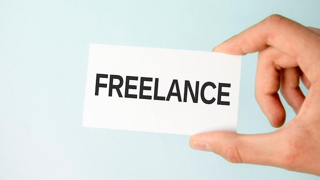 Mão do empresário segurando um cartão de visita de papel com o texto freelance, close-up fundo azul claro