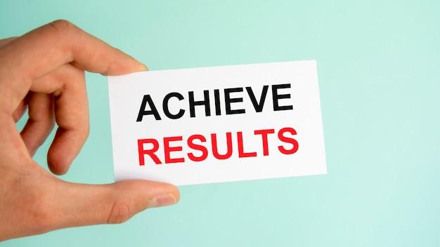 Mão do empresário segurando um cartão de visita de papel com texto alcançar resultados, close-up de fundo azul claro, conceito de negócio