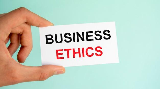 Mão do empresário segurando um cartão de visita de papel com texto sobre ética nos negócios, plano de fundo azul claro