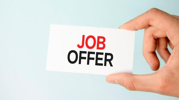 Mão do empresário segurando um cartão de visita de papel com uma oferta de trabalho em texto, plano de fundo azul claro closeup, conceito de negócio