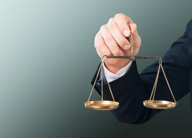 Mão do empresário segurando uma balança