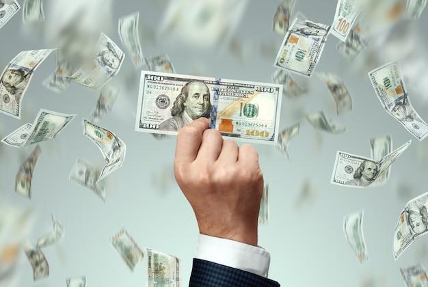 Mão do empresário segurando uma nota de cem dólares e dólares caindo, start-up.
