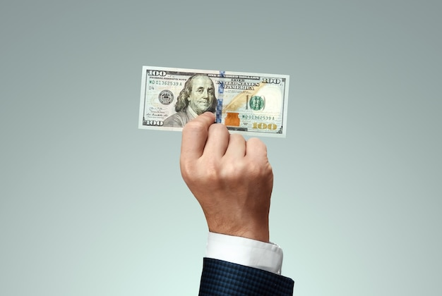 Mão do empresário segurando uma nota de cem dólares. o conceito de salário, investimento, doação.