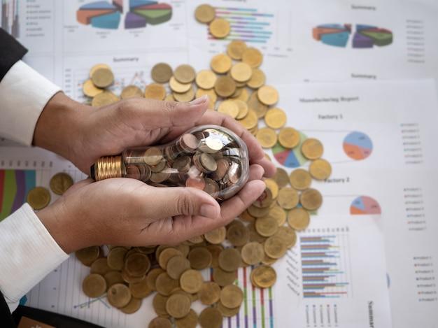 Mão do empresário segurar a lâmpada. economia de energia e economizar dinheiro