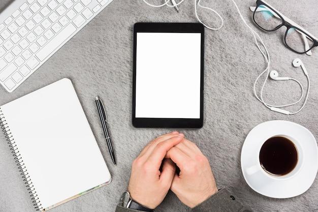 Mão do empresário sobre a mesa cinza com material de escritório