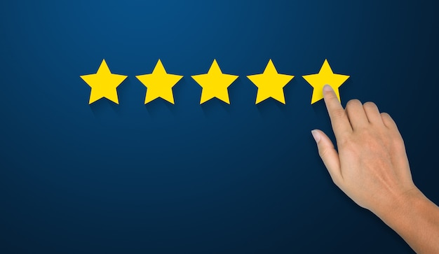 Mão do empresário tocando o símbolo de cinco estrelas para aumentar a classificação do conceito de empresa