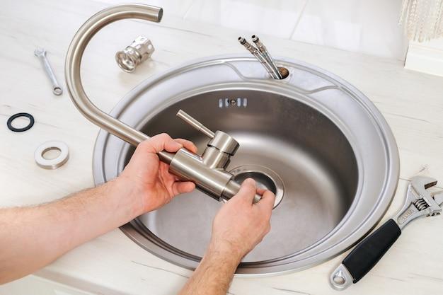Mão do encanador segura uma nova torneira para instalar na pia da cozinha