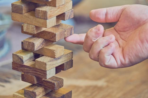 Mão do engenheiro jogando um jogo de blocos de madeira