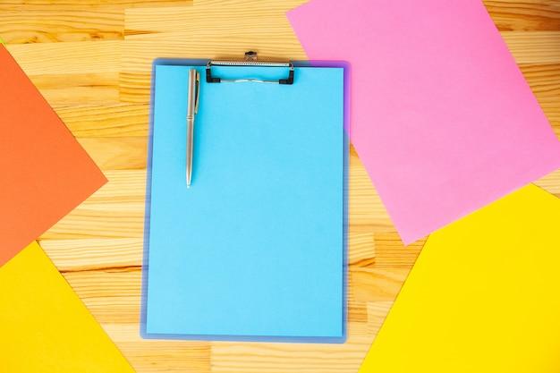 Mão do escritório que guarda um dobrador com um papel azul da cor no fundo da tabela de madeira.