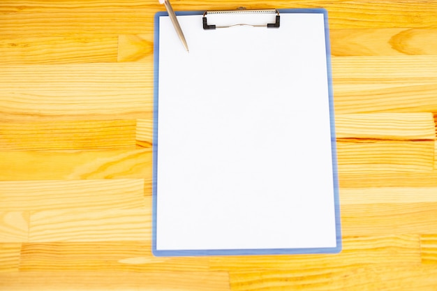 Mão do escritório que guarda um dobrador com um papel branco da cor no fundo da tabela de madeira.