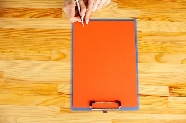 Mão do escritório que guarda um dobrador com um papel da cor vermelha no fundo da tabela de madeira. co