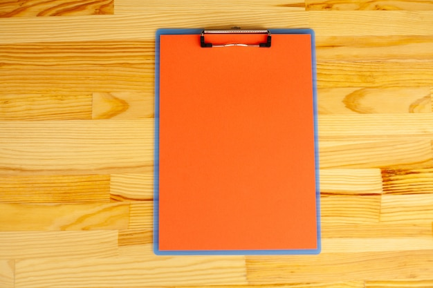 Mão do escritório que guarda um dobrador com um papel da cor vermelha no fundo da tabela de madeira.