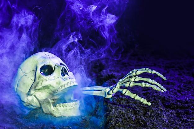 Mão do esqueleto azulado saindo do crânio no chão