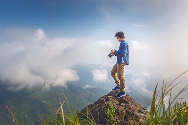 Mão do fotógrafo segurando a câmera e em pé no topo da rocha na natureza. conceito de viagens. tom vintage.