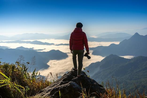 Mão do fotógrafo segurando a câmera e em pé no topo da rocha na natureza. conceito de viagens.