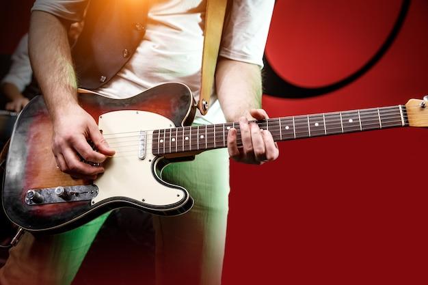 Mão do guitarrista tocar guitarra no palco do concerto com luz vermelha, instrumento musical praticando.