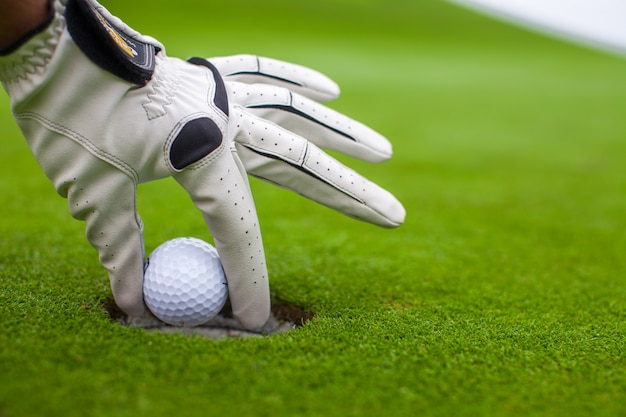Mão do homem, colocando uma bola de golfe no buraco no campo verde