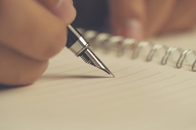 Mão do homem com escrita da pena no caderno. fechar-se