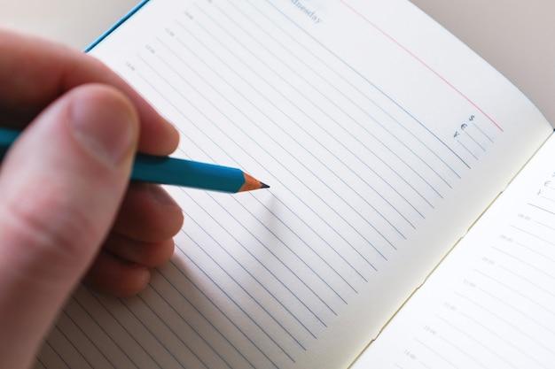 Mão do homem com escrita do lápis no caderno branco. conceito para educação e negócios