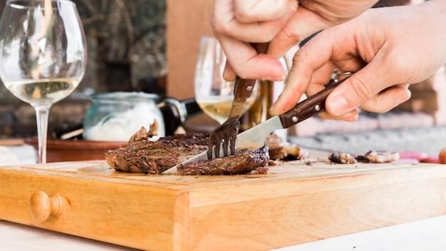 Mão do homem, corte o bife de carne com garfo e faca na tábua de cortar com gaveta