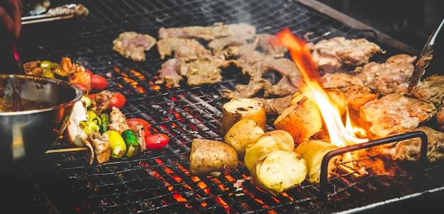 Mão do homem cozinhar churrasco grill / bife com fogo