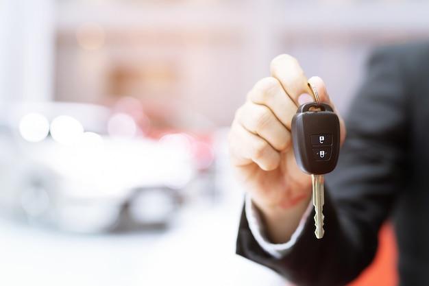 Mão do homem de negócio que guarda a parte dianteira da chave do carro com o carro na sala de exposições no fundo.