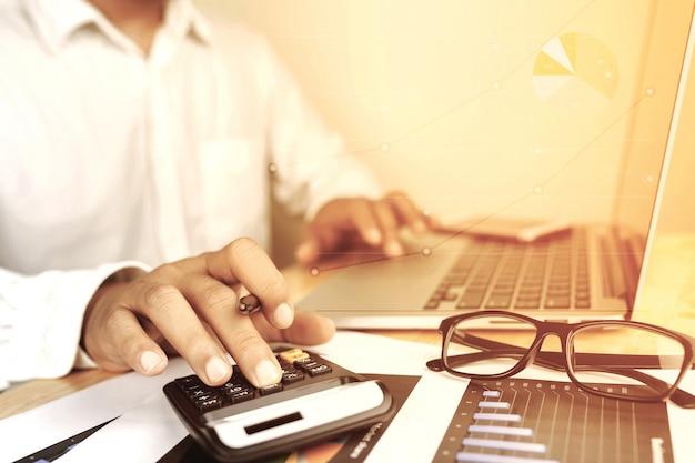Mão do homem de negócio que trabalha com o laptop no conselheiro de investimento empresarial de madeira da mesa.