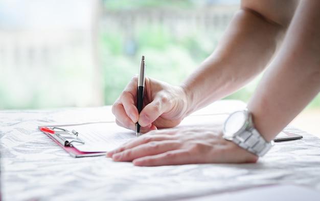 Mão do homem de negócios, assinando o documento de papel