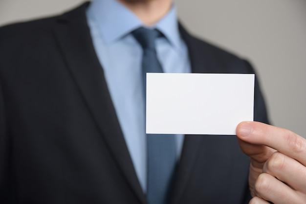 Mão do homem de negócios mostrando o cartão de visita