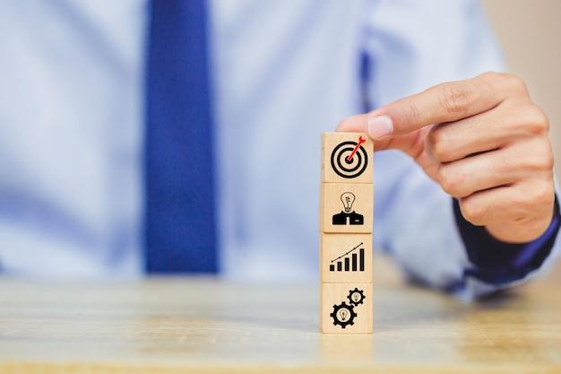Mão do homem de negócios que arranja o bloco de madeira com estratégia empresarial do alvo do ícone.
