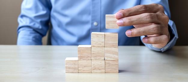 Mão do homem de negócios que coloca ou que puxa o bloco de madeira no edifício.