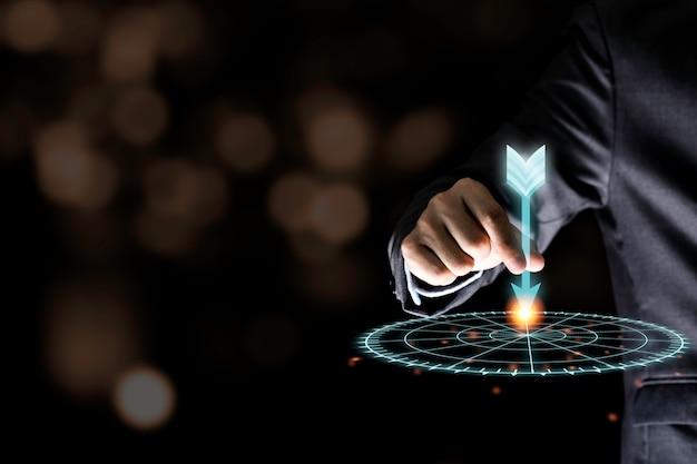 Mão do homem de negócios que guarda e que joga o dardo virtual para alvejar a placa na parede preta. conceito do alvo do negócio e do investimento.