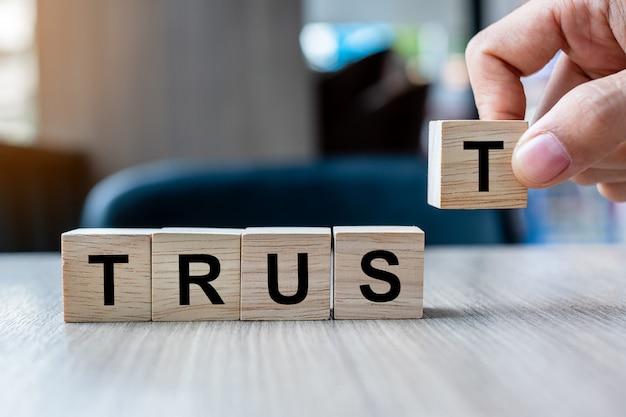 Mão do homem de negócios que guarda o bloco de madeira do cubo com palavra do negócio da confiança no fundo da tabela.