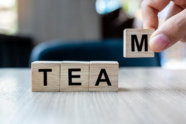 Mão do homem de negócios que guarda o bloco de madeira do cubo com palavra do negócio da equipe. cooperação, juntos, negócios e conceito de trabalho em equipe