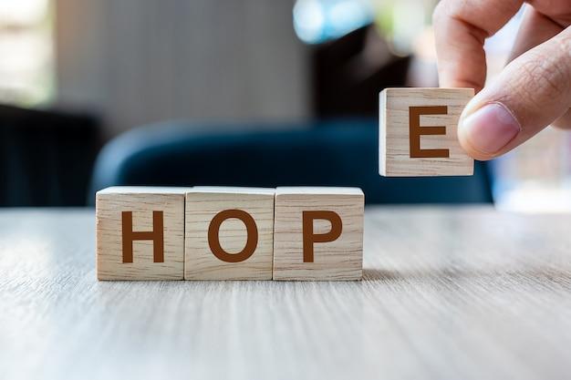 Mão do homem de negócios que guarda o bloco de madeira do cubo com palavra do negócio da esperança no fundo da tabela.